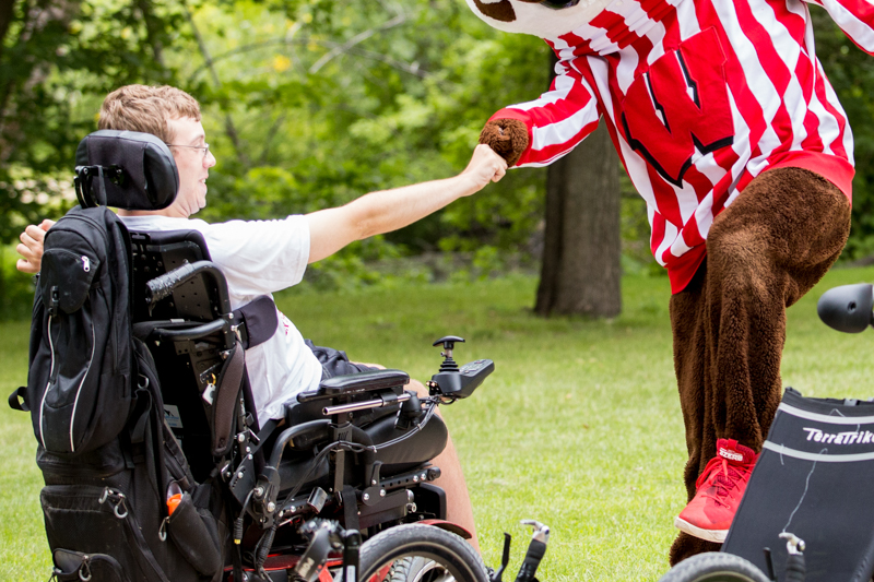 Bucky badger fist bumping a student in a wheelchair